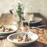 Table avec deux assiettes et deux verres de vin